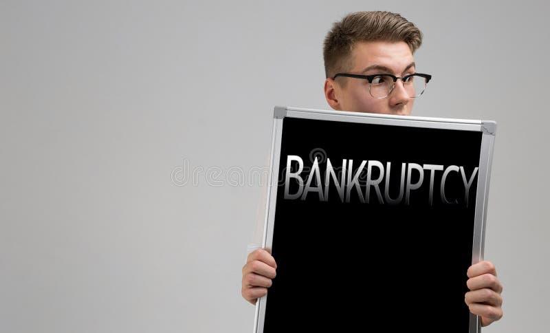 O homem novo mantém-se na frente dele que um cartaz com falência é isolado em um fundo claro fotos de stock royalty free