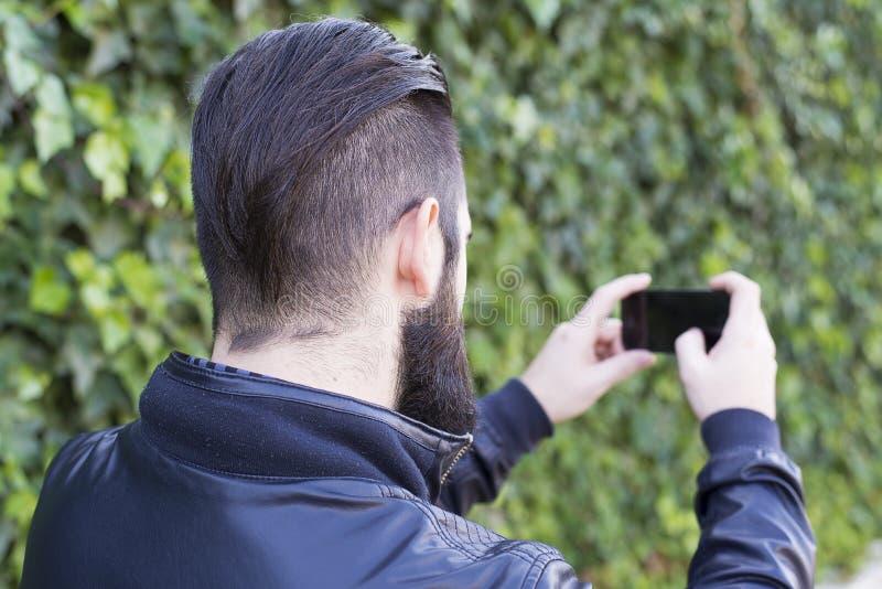 O homem novo moderno e farpado transforma-se um selfie imagens de stock