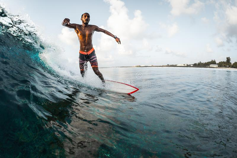 O homem novo monta a onda de oceano foto de stock