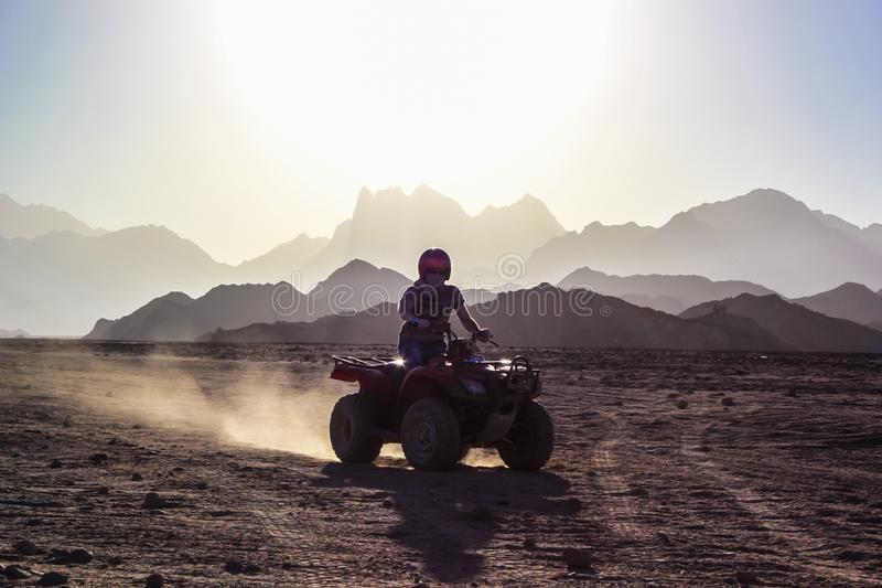 O homem novo monta um ATV no deserto sobre o fundo das montanhas no por do sol imagem de stock