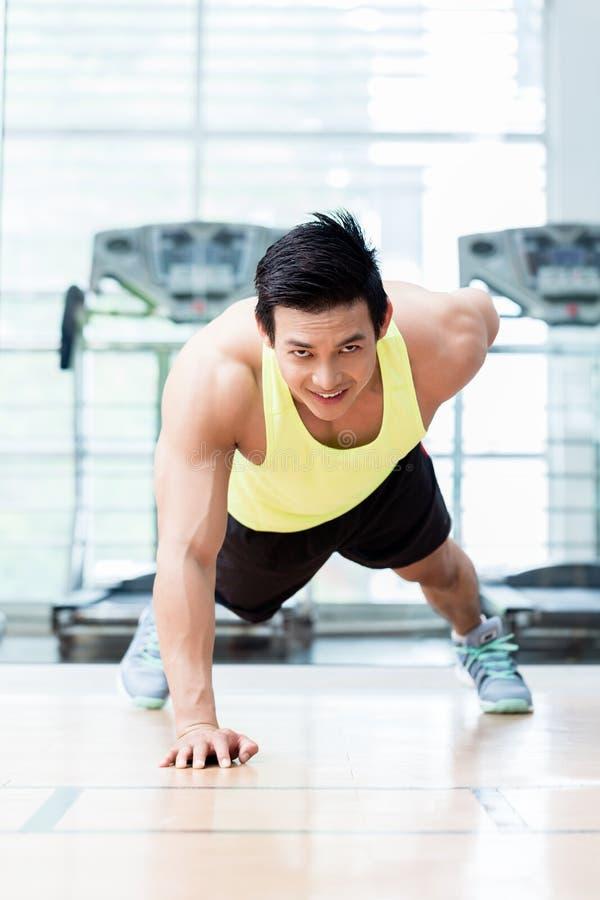 O homem novo muscular que faz um armou flexões de braço no gym imagens de stock royalty free