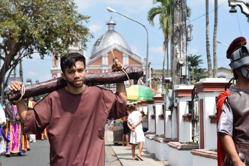O homem novo não identificado que joga o papel de logs levando do ladrão, drama da rua, a comunidade comemora o Sexta-feira Santa fotografia de stock