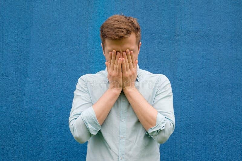 O homem novo na camisa azul fecha sua cara no esforço e na depressão imagem de stock royalty free