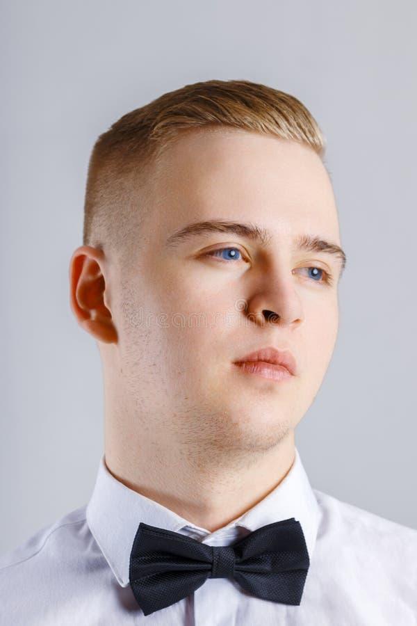 O homem novo na camisa branca e no laço preto levanta no estúdio fotos de stock
