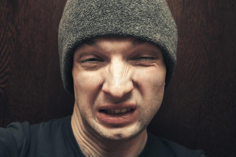 O homem novo no chapéu cinzento faz a cara feia fotos de stock royalty free