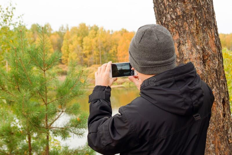 O homem novo no revestimento preto e no chapéu feito malha cinza está tomando uma foto da paisagem do outono no telefone celular  fotos de stock royalty free