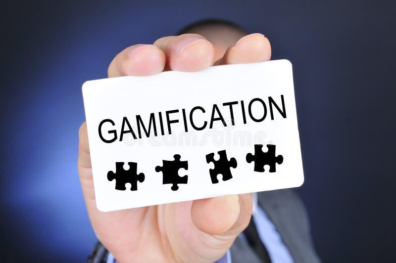 O homem novo no terno mostra um quadro indicador com o gamification da palavra imagem de stock