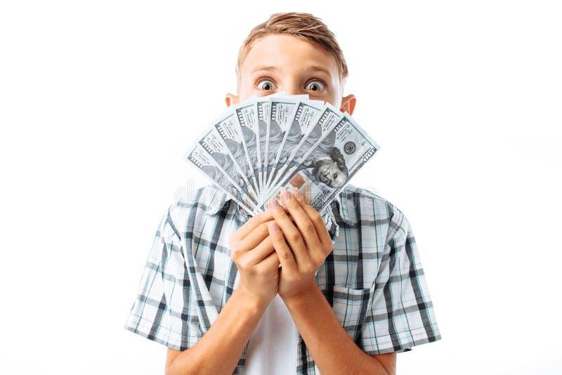 O homem novo nos vidros guarda muito cem notas de dólar na frente da cara, ascendente próximo da cara, no estúdio no fundo branco fotografia de stock royalty free