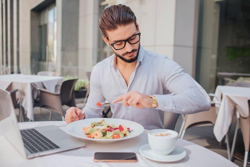 O homem novo ocupado senta-se na tabela fora do restaurante Olha relógios Há portátil, bacia de salada, telefone e copo de foto de stock