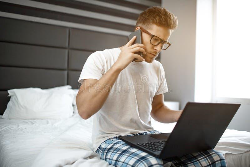 O homem novo ocupado senta-se no amanhecer da cama Guy Talk no telefone Olha no portátil e no tipo no teclado sério e fotos de stock royalty free