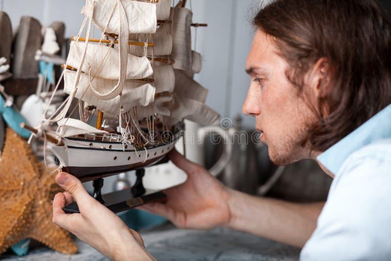 O homem novo olha o modelo do navio de navigação no interior do vintage fotografia de stock