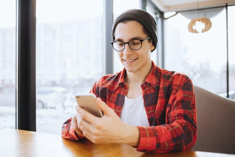 O homem novo ou o freelancer atrativo estão sentando-se no café durante a ruptura de café imagens de stock royalty free