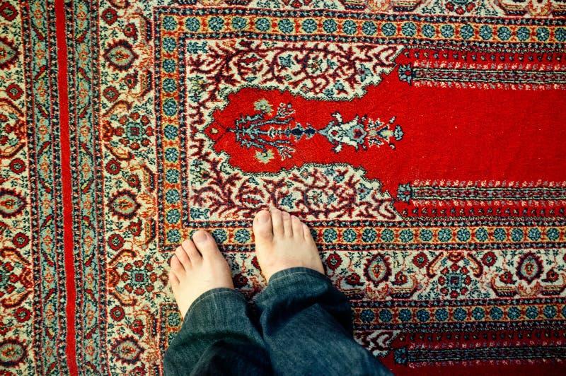 O homem novo paga a posição em um assoalho da mesquita imagens de stock