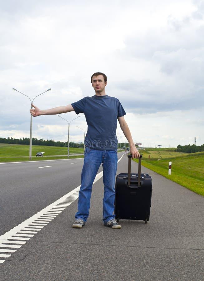 O homem novo pendente na estrada com uma mala de viagem fotografia de stock royalty free
