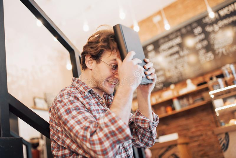 O homem novo pensativo está sentando-se na loja dos confeitos Está bebendo o café ao esperar alguém foto de stock