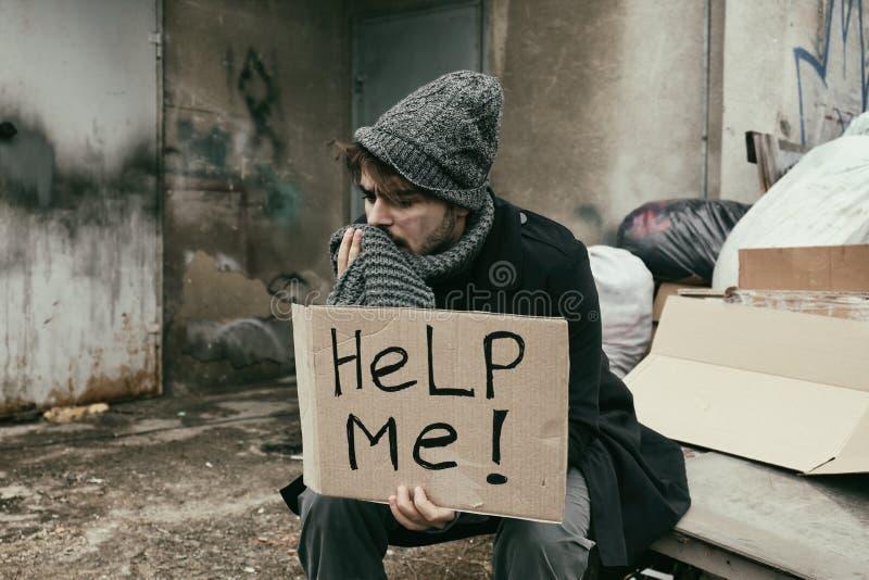 O homem novo pobre com AJUDA-ME a assinar fotografia de stock royalty free