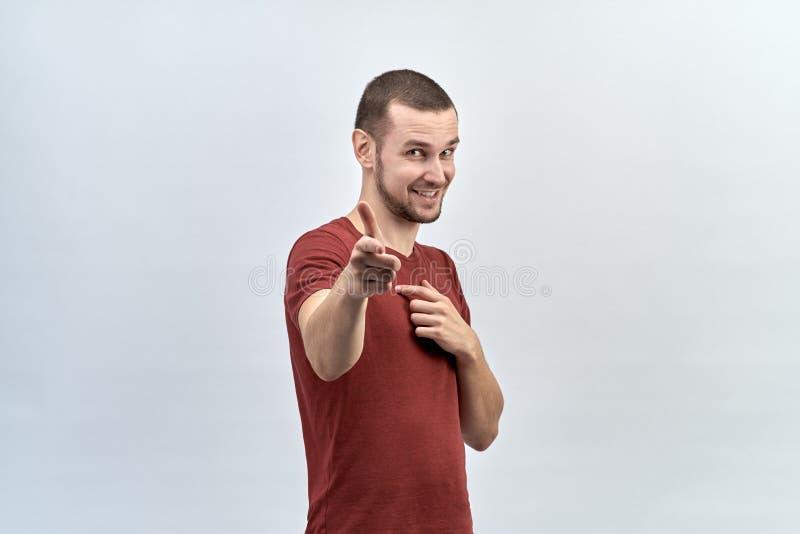 O homem novo positivo seguro com cabelo curto mostra o indicador à câmera foto de stock