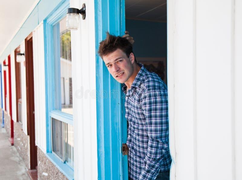 O homem novo olha fora da sala de motel imagem de stock