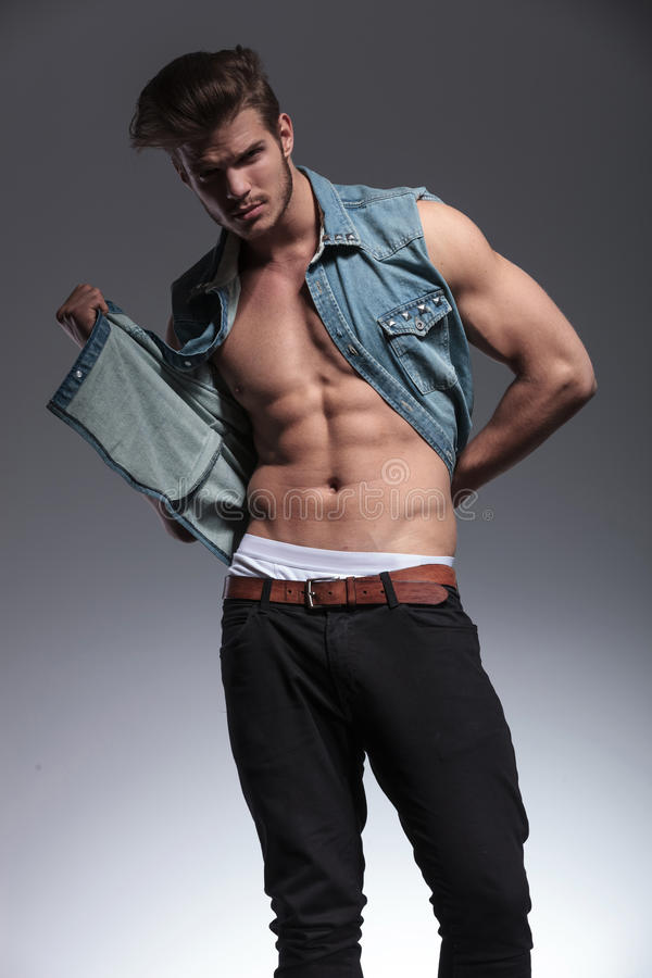 O homem novo puxa sua veste das calças de brim foto de stock