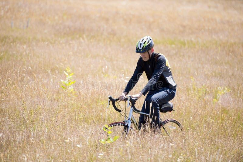 O homem novo que dá um ciclo para fora na bicicleta monta através do campo foto de stock royalty free