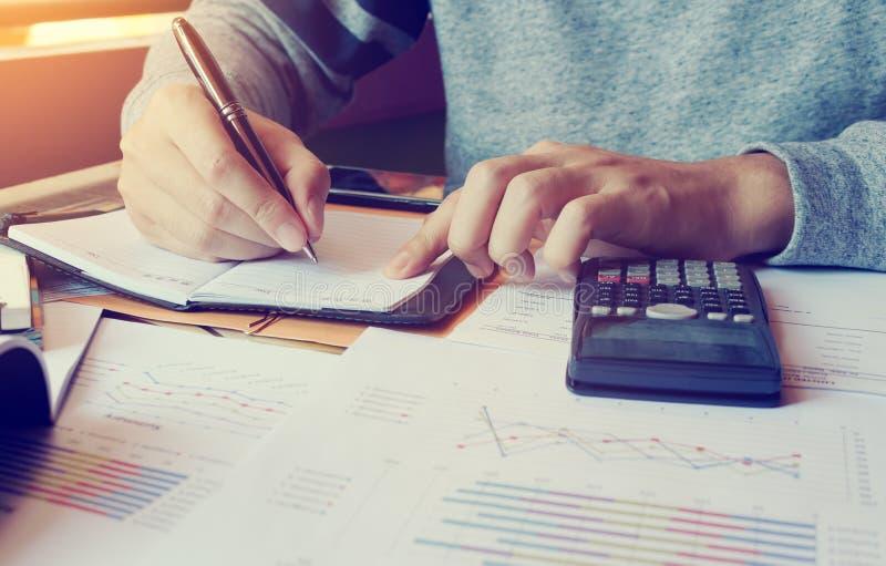 O homem novo que faz a finança no escritório domiciliário com calcula sobre o custo imagem de stock royalty free