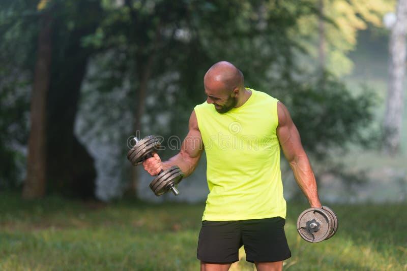 O homem novo que faz o exercício para o bíceps fora malha imagens de stock royalty free