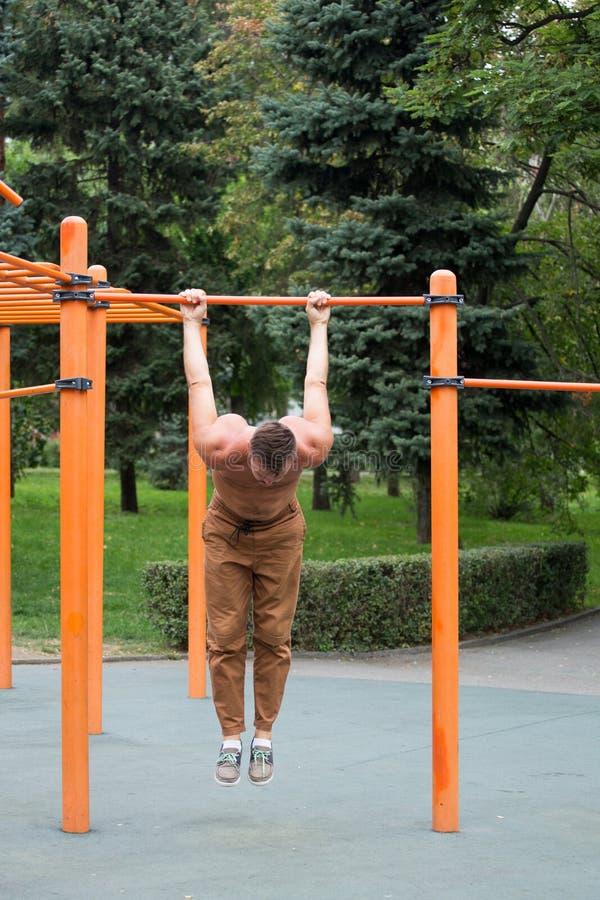 o homem novo que faz a tração levanta na barra horizontal fora fotografia de stock