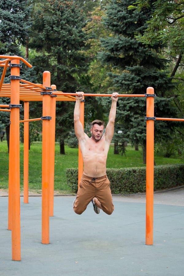 o homem novo que faz a tração levanta na barra horizontal fora fotografia de stock royalty free