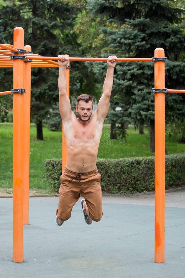 o homem novo que faz a tração levanta na barra horizontal fora fotos de stock