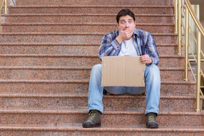 O homem novo que implora o dinheiro na rua fotografia de stock