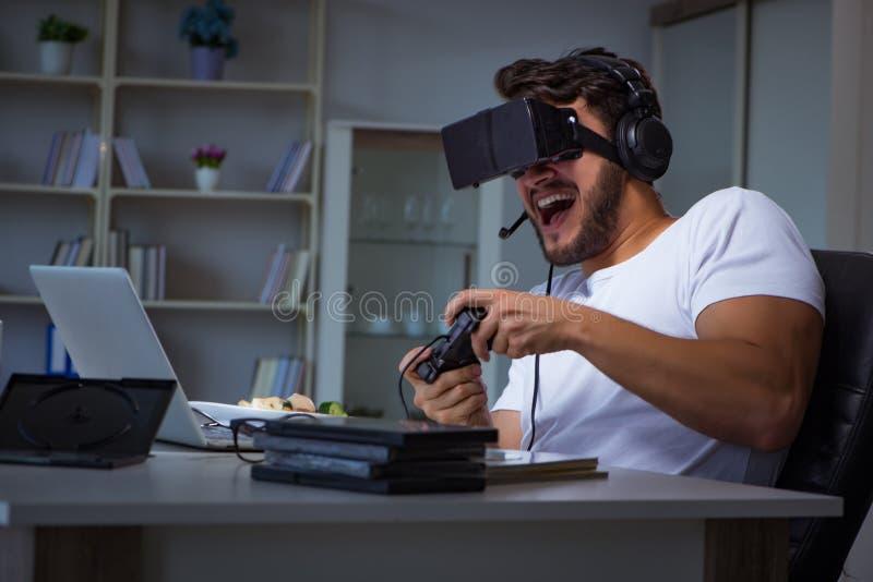 O homem novo que joga o muito tempo dos jogos tarde no escritório fotos de stock