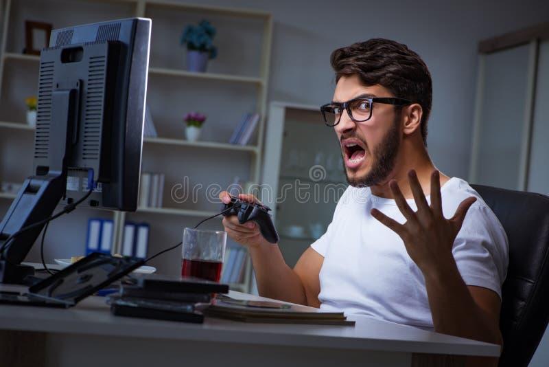 O homem novo que joga o muito tempo dos jogos tarde no escritório foto de stock royalty free