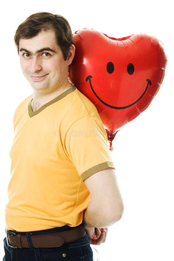O homem novo que prende um coração vermelho deu forma ao balão foto de stock royalty free