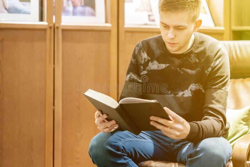 O homem novo que senta em casa a biblioteca e leu um livro, refrigerou e relaxou f fotos de stock royalty free