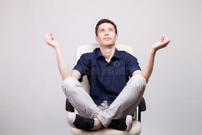O homem novo que sentam-se em uma cadeira do escritório com seus pés acima na cadeira e as mãos em um relaxamento levantam foto de stock