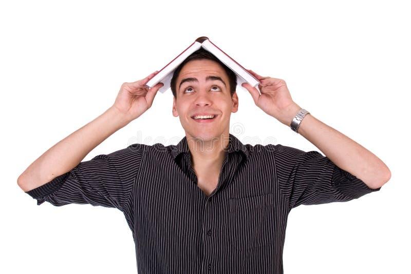 O homem novo que sorri com o livro em seu teve foto de stock royalty free