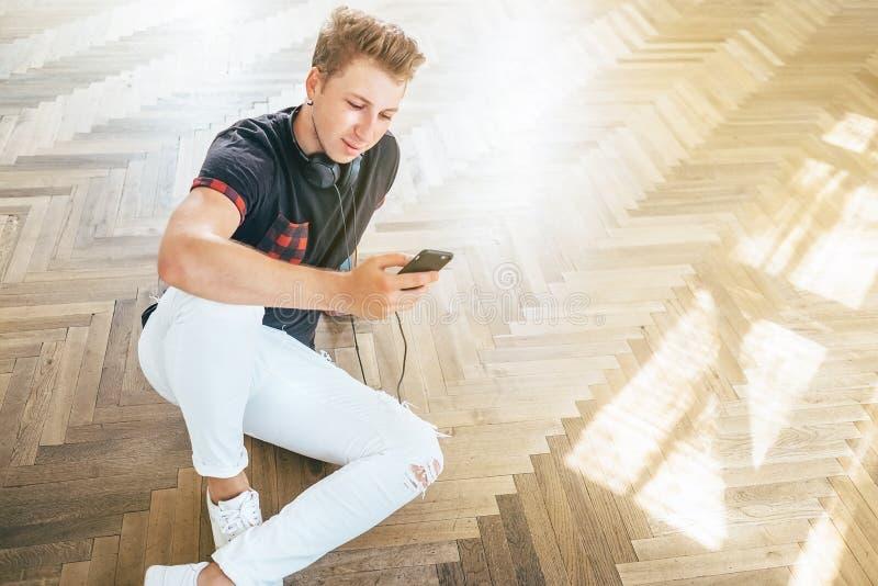 O homem novo que usa seu smartphone com fones de ouvido, escuta a m?sica e senta-se no assoalho imagem de stock