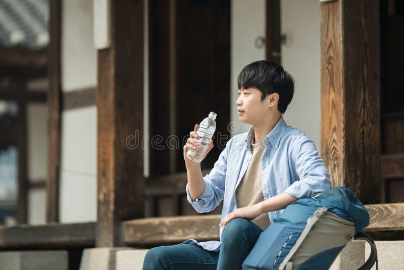 O homem novo que viaja a Coreia está tomando um resto com uma garrafa de água imagens de stock royalty free