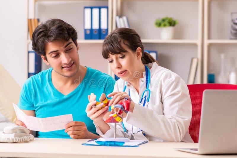 O homem novo que visita o cardiologista fêmea do doutor fotografia de stock