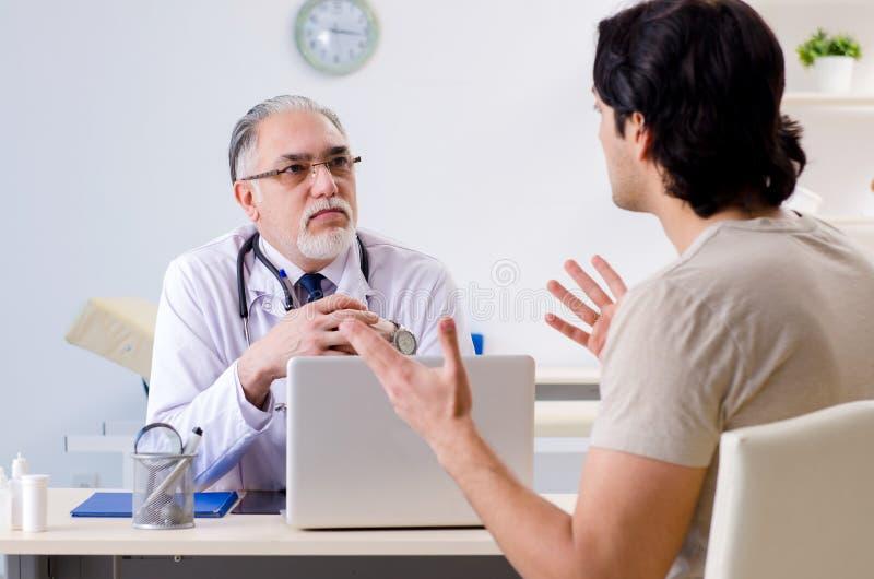 O homem novo que visita o doutor masculino idoso imagens de stock
