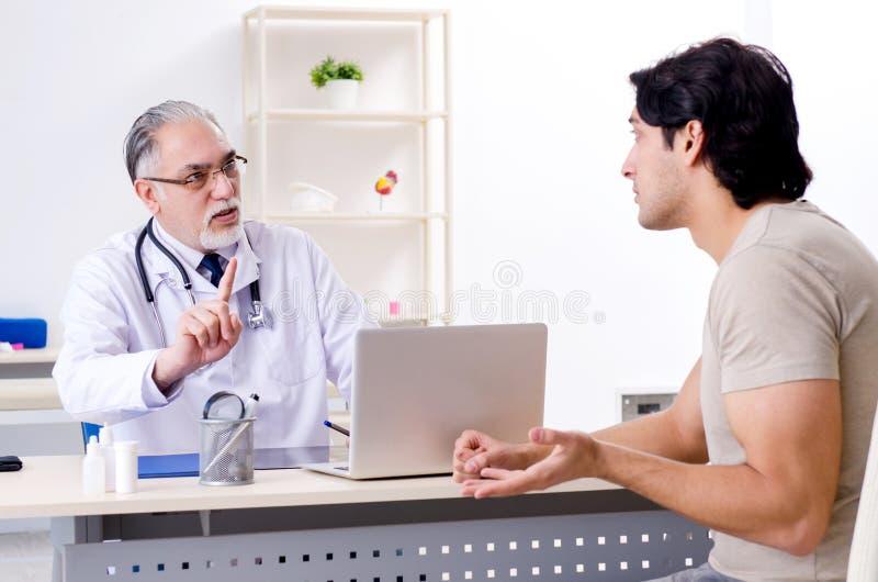 O homem novo que visita o doutor masculino idoso imagem de stock royalty free