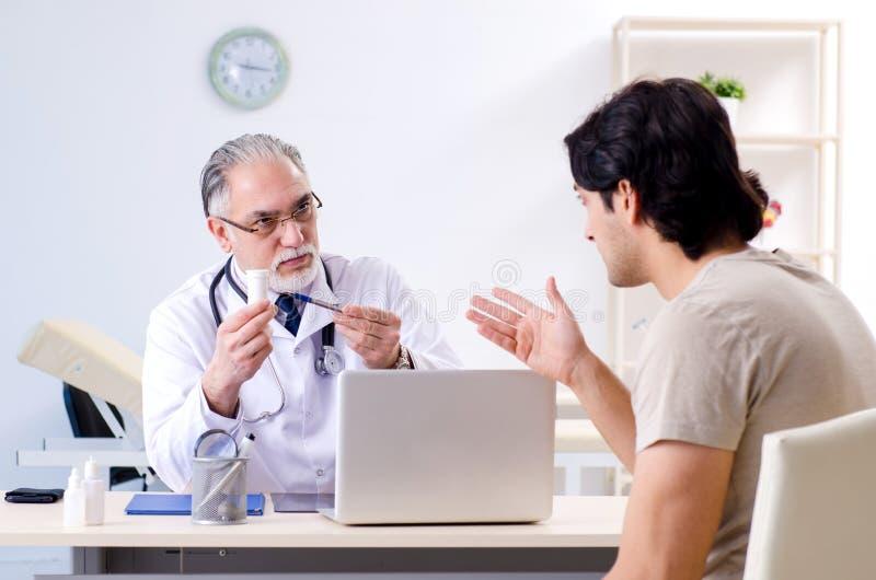 O homem novo que visita o doutor masculino idoso foto de stock