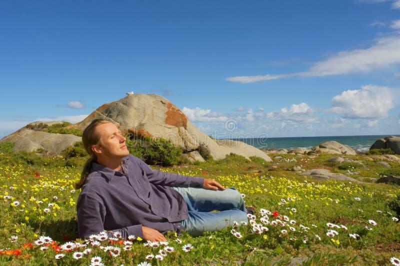 O homem novo relaxa o encontro no campo de flor fotos de stock