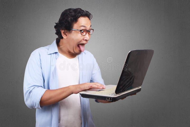 O homem novo remove seu Tounge, expressão engraçada que olha Lapto imagem de stock royalty free