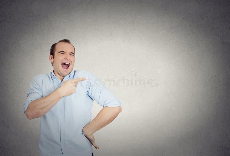 O homem novo, rindo, apontando com dedo, arma-se em alguém foto de stock royalty free