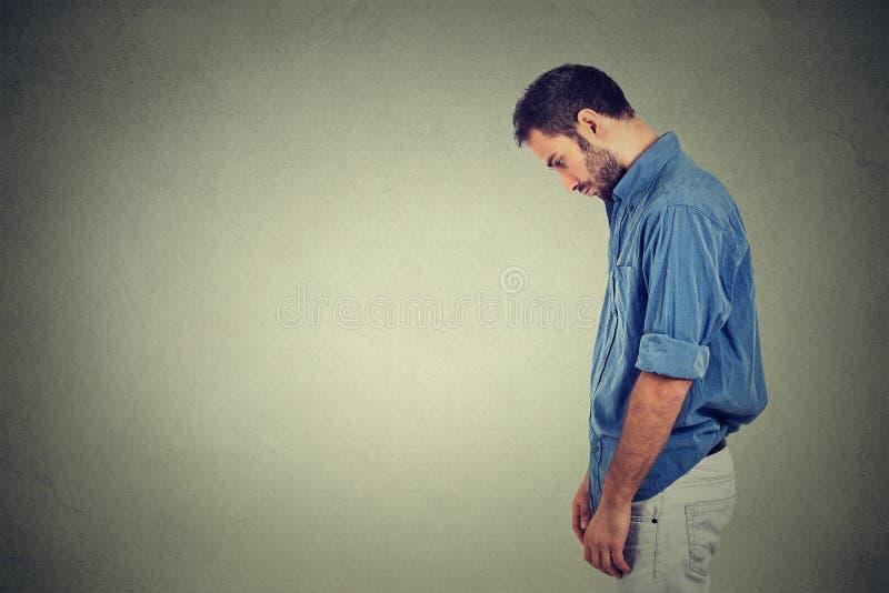 O homem novo só triste que olha para baixo não tem nenhuma motivação da energia na vida comprimida imagens de stock