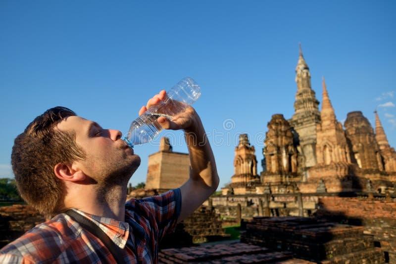 O homem novo sedento está bebendo a água engarrafada no templo do buddhism em Tailândia foto de stock royalty free