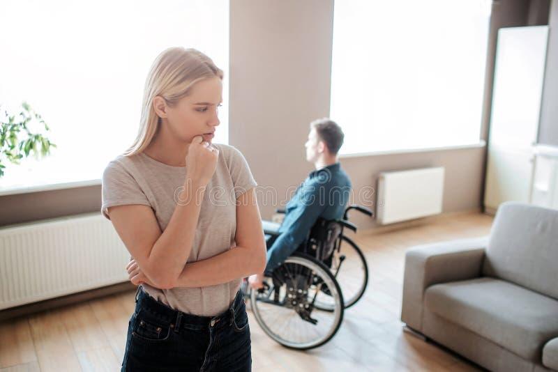 O homem novo senta-se com necessidades especiais senta-se na cadeira de rodas e no olhar na janela Suporte da mulher na parte dia imagem de stock