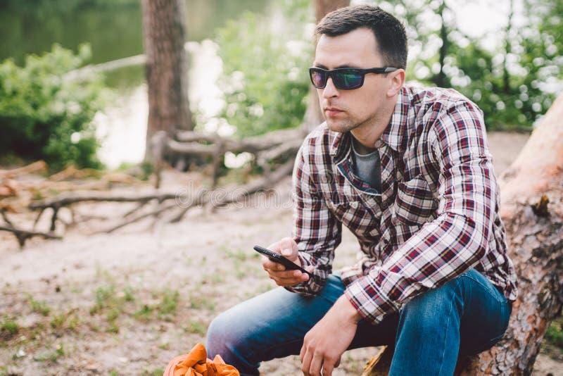 O homem novo senta-se no caminhão na floresta e telefone celular da utilização o viajante do homem senta-se na grande árvore caíd fotografia de stock royalty free