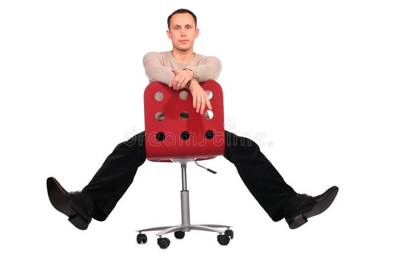 O homem novo senta-se nos pés da propagação da cadeira imagem de stock royalty free